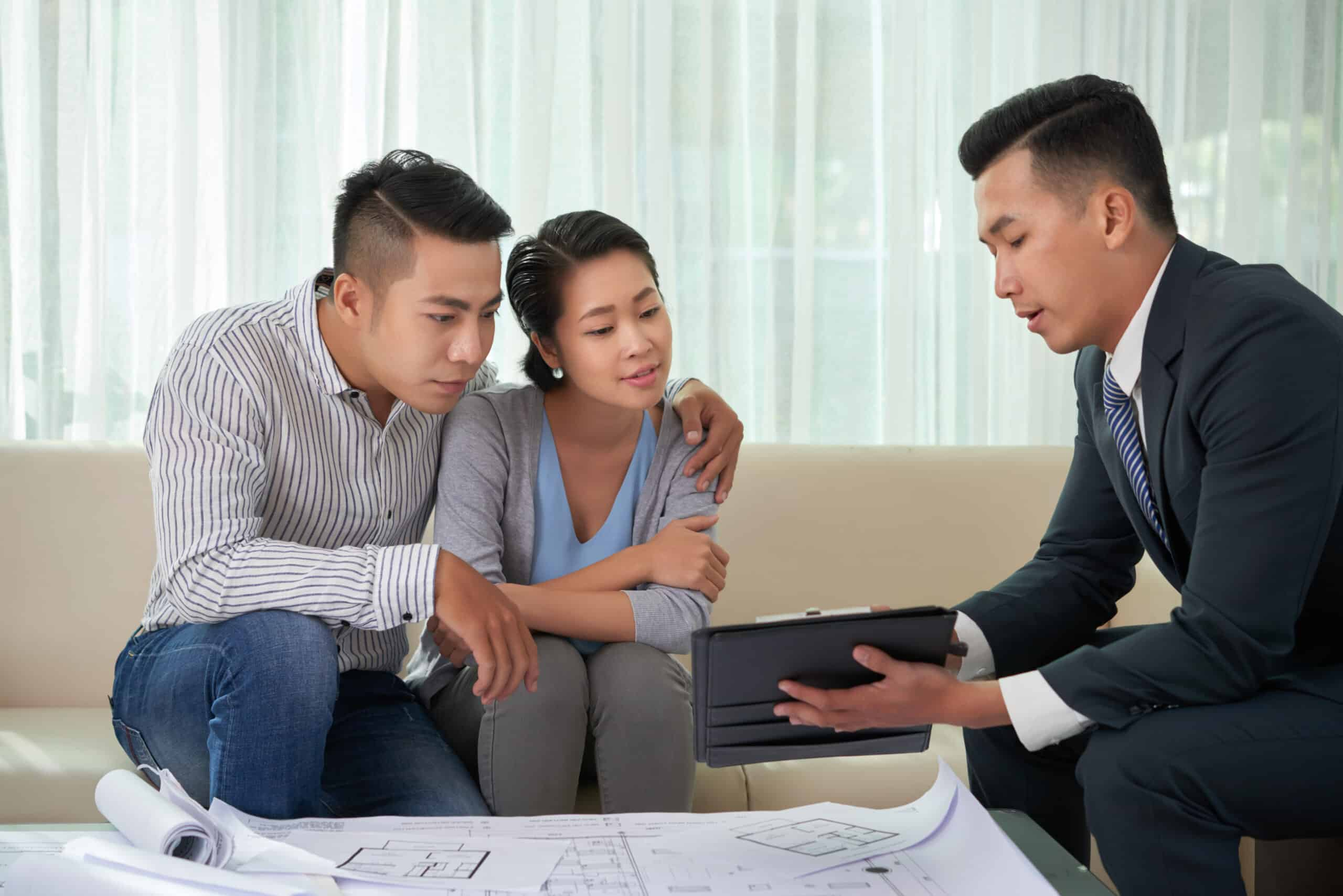 Real estate broker showing photos of house on digital tablet to young couple