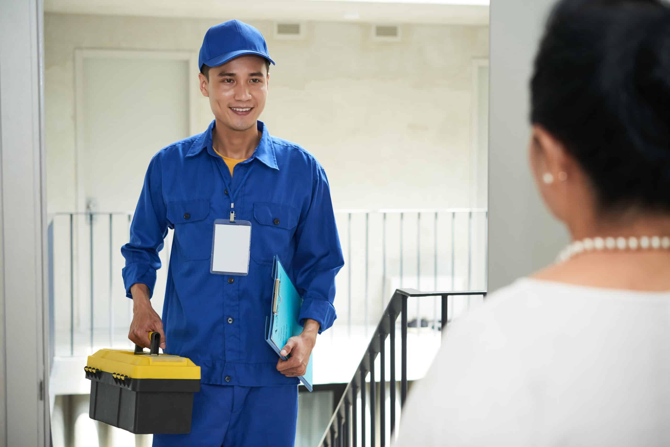 Cheerful Vietnamese handyman coming to home of senior woman to repair something